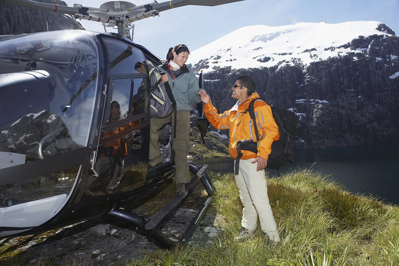 Hikers climbing out of helicopter on mountain top
